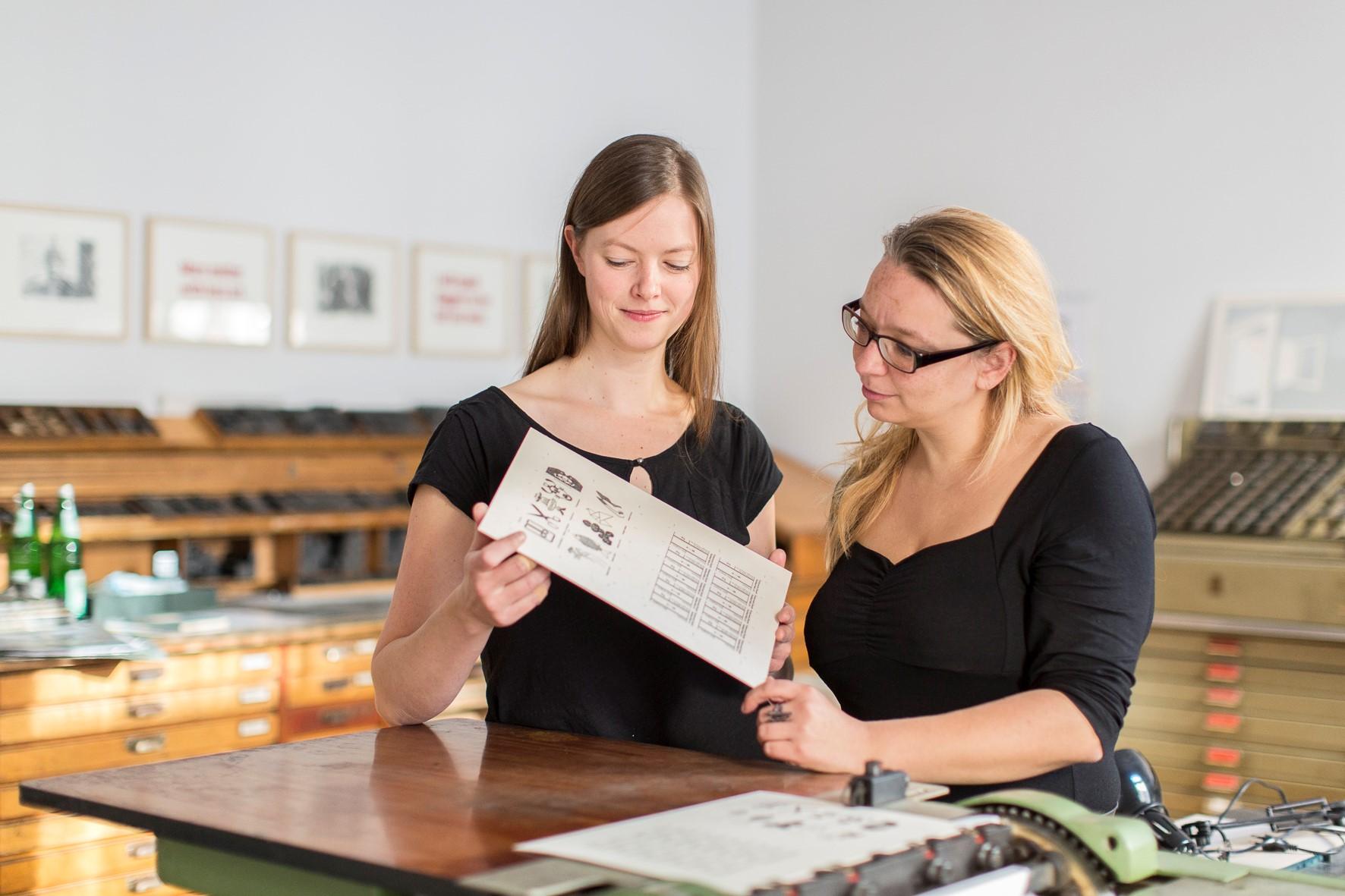 Annegret Rouél und Kathleen Hirschnitz mit dem Andruck der ersten KUNSTWIEGEKARTEN in der Druckwerkstatt des book art center halle. Foto: Matthias Ritzmann.